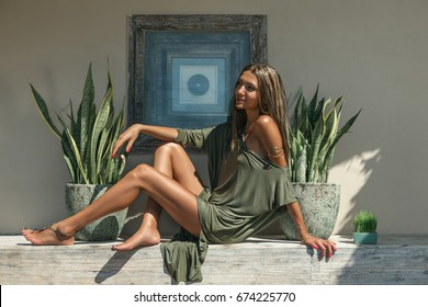 Beautiful young woman wearing in green dress with large green leafs. Natural organic vegan concept.