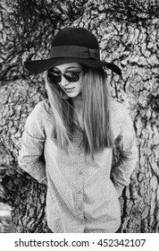 Beautiful young woman wearing in hat and sunglasses standing on background of tree trunk. Monochrome image