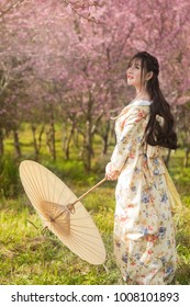 Beautiful young woman wearing kimono (traditional japanese dresses) with umbrella, sakura (cherry blossoms) background