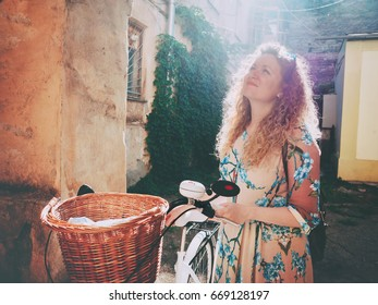 Beautiful young woman wearing long dress standing near retro white bicycle with basket and looking on arch in old courtyard