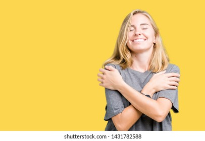 Beautiful young woman wearing oversize casual t-shirt over isolated background Hugging oneself happy and positive, smiling confident. Self love and self care