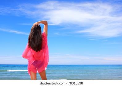 Beautiful young woman wearing a pink shirt enjoying the summer sun by the beach