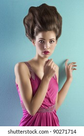 beautiful young woman wearing a pink elegant evening dress and with a high fashion hair up-do standing in front of a turquoise background