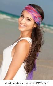 Beautiful young woman wearing a purple bandana enjoying the South Beach shoreline in Miami.