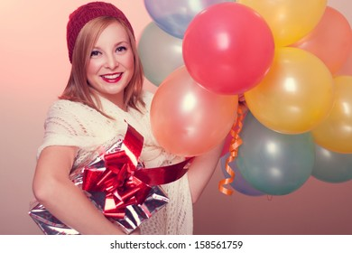 Beautiful young woman wearing red gloves and scarf holding balloons and gift.