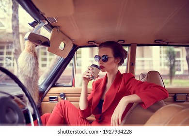 Beautiful young woman wearing red costume and sunglasses sitting in retro car and drink coffee