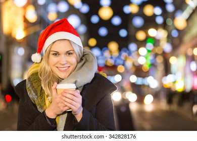 Beautiful young woman wearing Santa hat in London. She is blonde, on her early twenties, holding a cup of coffee and wearing warm clothes. On background there are many Christmas lights.