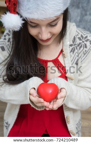 Beautiful young woman Wearing a Santa hat With Christmas trees Hold red  heart in hand in 2e5ea8710dc