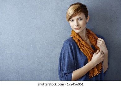 Beautiful young woman wearing scarf standing by grey wall, looking at camera. Copy space.