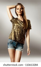 Beautiful young woman wearing shorts and glitter blouse