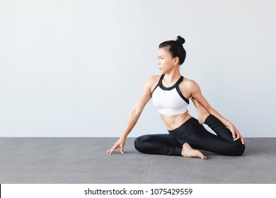 Beautiful Young Woman Wearing Sportswear Practicing Yoga In Studionatural LightOne Legged