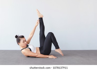 Beautiful Young Woman Wearing Sportswear Practicing Yoga In Studionatural LightWind Release Pose