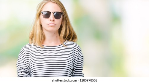 a5d8a2e226 Beautiful young woman wearing sunglasses over isolated background with  serious expression on face. Simple and