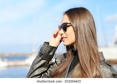 Beautiful young woman wearing sunglasses at seashore on sunny autumn day