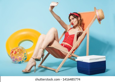 Beautiful young woman wearing swimsuit relaxing on a deck chair with cooler and inflatable ring isolated over blue background, taking a selfie