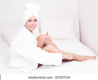 beautiful young woman wearing a towel and a white bathrobe and applying body lotion, in bed at home