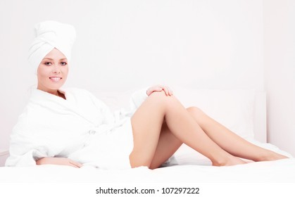 beautiful young woman wearing a towel and a white bathrobe in bed at home