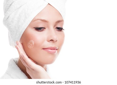 beautiful young woman wearing a towel and a white bathrobe applying cream on her face, isolated against white background, copyspace to the right