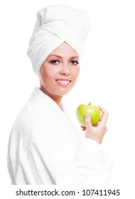 beautiful young woman wearing a towel and a white bathrobe and holding a green apple, isolated against white background