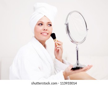beautiful young woman wearing a towel and a white bathrobe and holding a brush and mirror, isolated against white background
