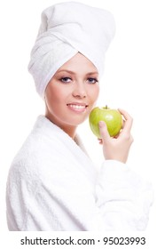 beautiful young woman wearing a towel and a white bathrobe and holding an apple, isolated against white background