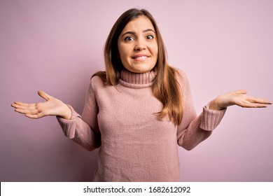 Beautiful young woman wearing turtleneck sweater over pink isolated background clueless and confused expression with arms and hands raised. Doubt concept.