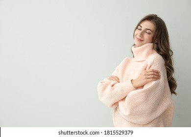 Beautiful young woman wearing warm pink sweater on light background. Space for text