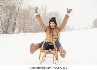 Beautiful young woman wearing a warm winter clothes, sitting on a sleigh and sliding down the hill, having fun on a snowy winter day
