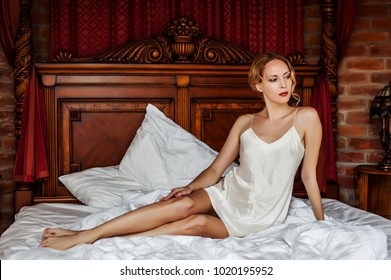 Beautiful young woman wearing white silk night lingerie a lies on bed in retro bedroom
