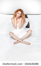 Beautiful young woman wearing white silk night lingerie a lies on bed in modern bedroom