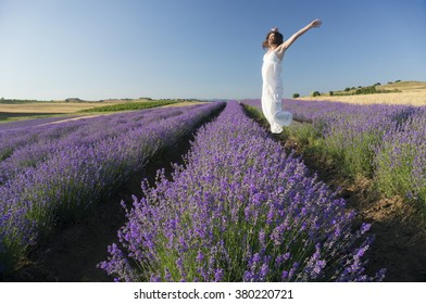 Beautiful young woman wearing a white dress jumping with joy in the middle of a lavender field in bloom.