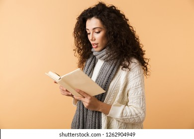 Beautiful young woman wearing winter scarf standing isolated over beige background, reading a book