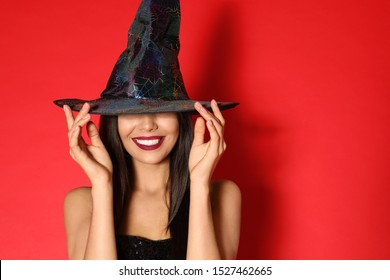 Beautiful young woman wearing witch costume for Halloween party on red background, space for text