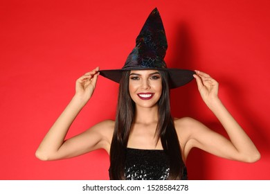 Beautiful young woman wearing witch costume for Halloween party on red background