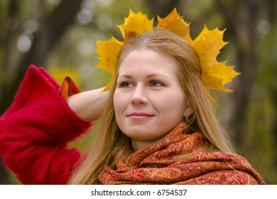 Beautiful young woman wearing ma?le wreath looking away with sad smile