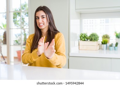 Beautiful young woman wearing yellow sweater disgusted expression, displeased and fearful doing disgust face because aversion reaction. With hands raised. Annoying concept.