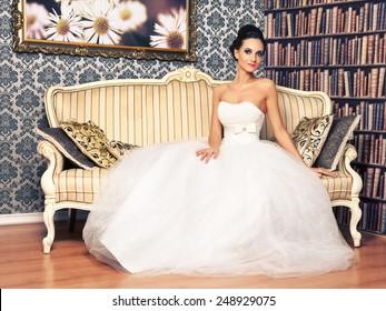 beautiful young woman in wedding dress sitting on sofa