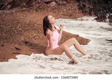 Beautiful young woman with wet hair and pink swimsuit on sand beach at sunset in waves