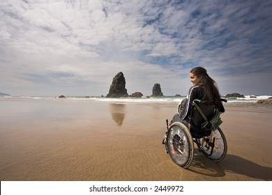 Beautiful young woman in a wheel chair visiting Cannon Beach in Oregon, USA.