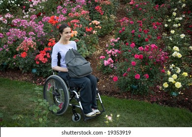 Beautiful young woman in a wheelchair visiting a rose garden in Oregon.