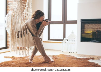 Beautiful young woman, which is wearing cashmere nightwear clothes, drinking tea or coffee while relaxing on rocking chair in scandinavian cabin near electric heater fireplace one lazy weekend morning