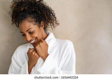 Beautiful young woman in a white bath robe isolated on beige background with copy space. Happy african girl in bathrobe against light brown wall. African american woman enjoy after body treatment.