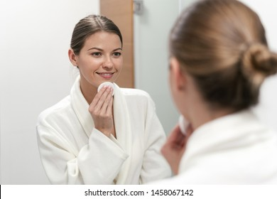 Beautiful and young woman in white bathrobe holding cotton pad in hands, looking at mirror in bathroom and remove make up from face