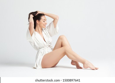 Beautiful young woman woman in white bathrobe on white background. Skin and body care concept