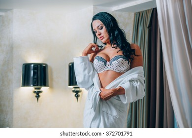 Beautiful young woman in white bathrobe  bedroom at home