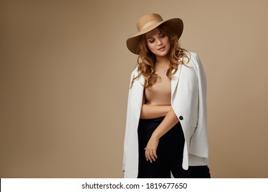 Beautiful young woman in white blazer and brown hat. Plus size model.