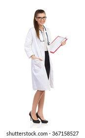 Beautiful young woman in white coat and glasses holding clipboard and posing with hand in pocket. Full length studio shot isolated on white.