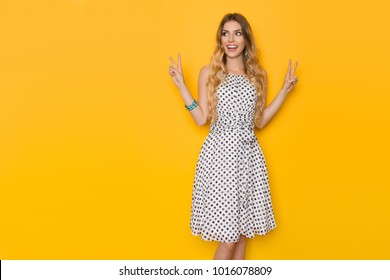Beautiful young woman in white dotted summer dress is  showing peace hand sign, looking away and smiling. Three quarter length studio shot on yellow background.