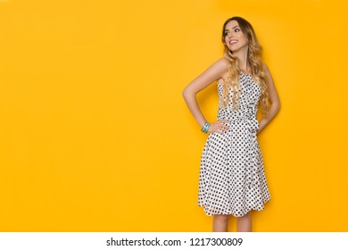 7546187c6bb1 Beautiful young woman in white dotted summer dress is posing with hands on  hip