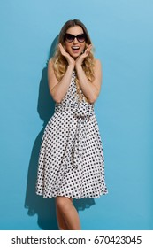 Beautiful young woman in white dotted summer dress and sunglasses is holding head in hands, shouting and looking at camera. Three quarter length studio shot on blue background.